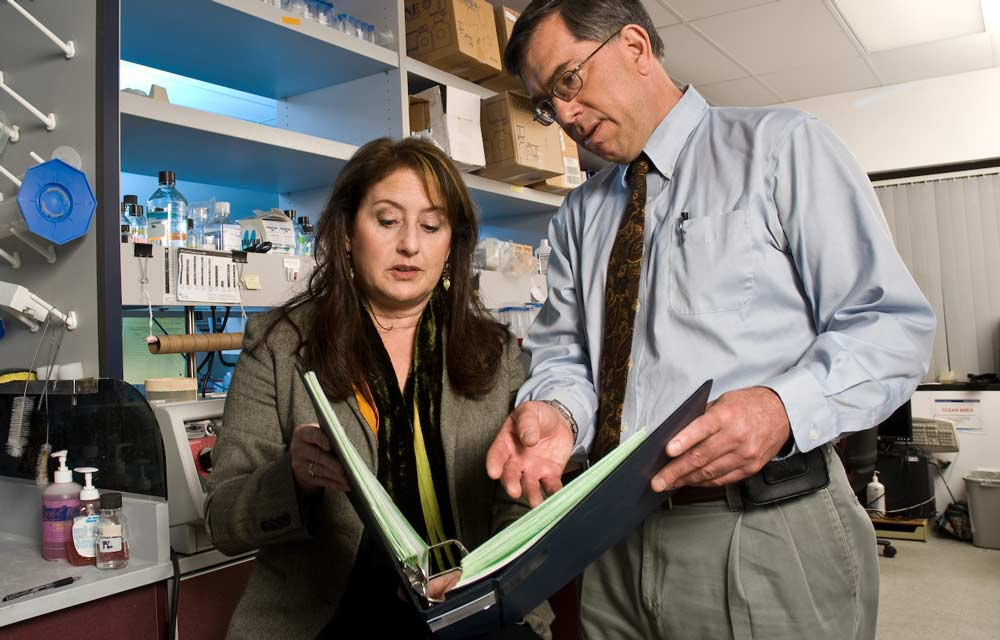 man and woman looking at binder in lab