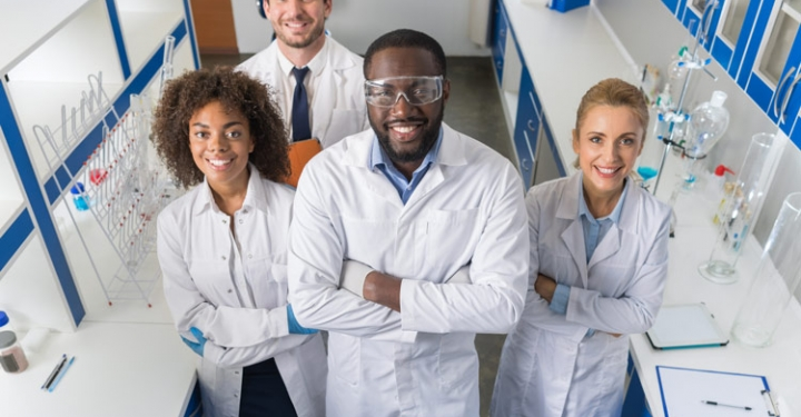 Mix Race Team Of Scientific Researchers In Lab Wearing White Coats And Protective Glasses