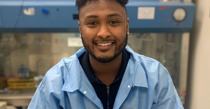 Daniel Million in lab wearing lab coat and smiling