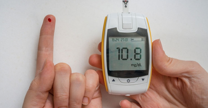 Diabetic patient is using glucometer to check glucose level