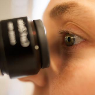 close up of person looking into microscope eyepiece