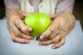 Hands with joints made swollen and stiff by rheumatoid arthritis, holding an apple