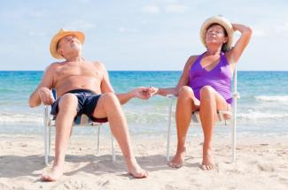 happy retired senior couple sitting on the beach holding hands and enjoying summer vacations